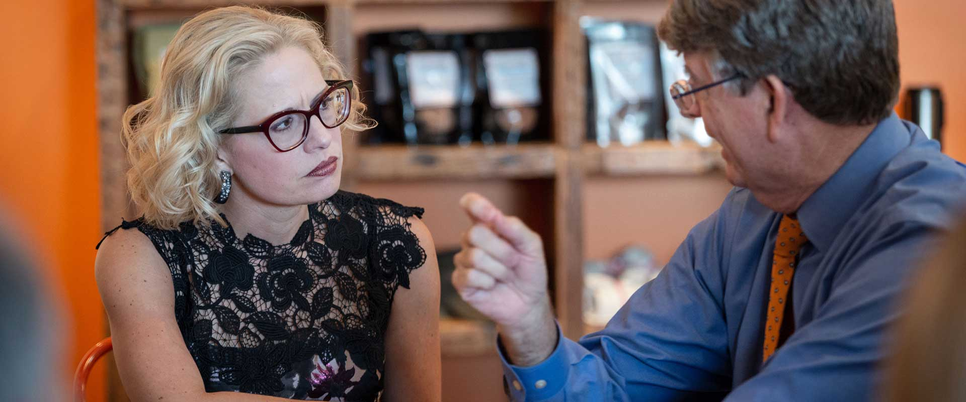 Photo of Senator Sinema listening to a constituent